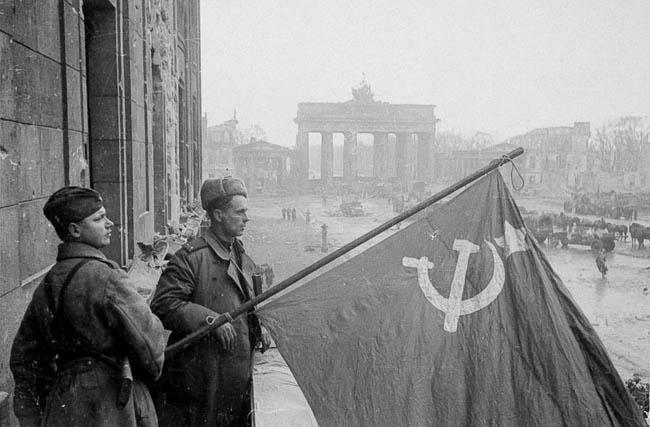Советские военные — рядовой и лейтенант — со знаменем в Берлине на фоне Бранденбургских ворот, 1945 г.