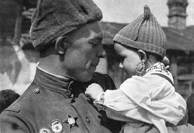 Советский солдат с чешским ребенком на руках. Малыш рассматривает орден Славы на груди бойца. Прага, май 1945 г.
