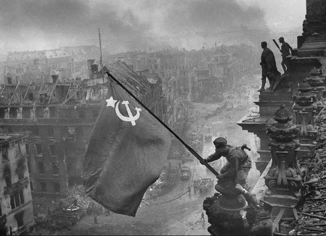 Фотография советского солдата, водружающего над взятым Рейхстагом красное знамя
