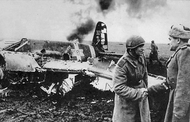 Советский офицер поздравляет командира зенитной батареи, сбившей румынский штурмовик немецкого производства, апрель 1943 г.