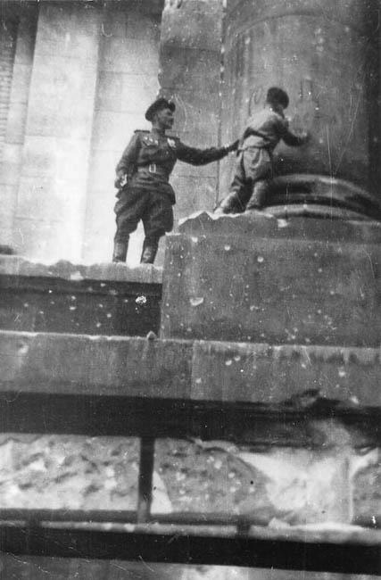 Сын полка Володя Тарновский ставит автограф на колонне Рейхстага. Он написал: «Северский Донец — Берлин», и расписался — за себя, командира полка и своего однополчанина, который его поддерживал, май 1945 г.