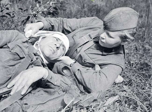 Сандружинница Скотинкина С.Г. перевязывает раненого бойца. Северо-Западный фронт, 1942 г.