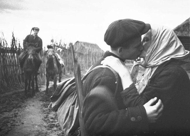Колхозница одного из сел отправляет своего сына в партизанский отряд. Ленинградская область, 1942 г. Автор съемки: Трахман М. А.