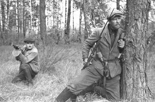 Партизаны одного из отрядов сидят в засаде на лесной дороге.