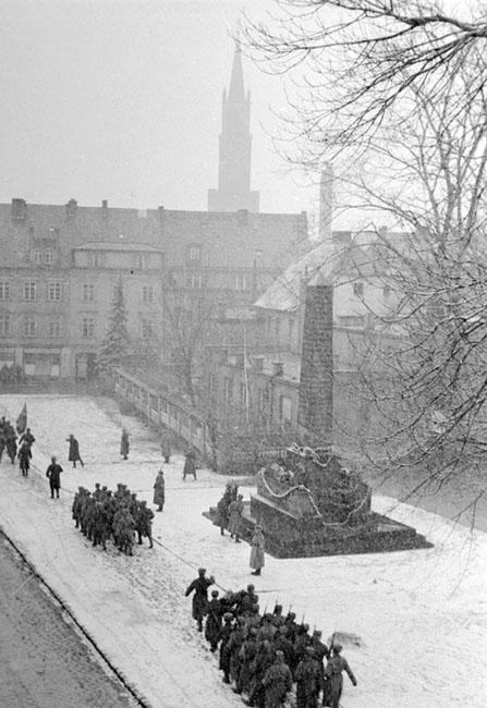 Советские бойцы проходят строем мимо памятника, под которым, по легенде, захоронено сердца М.И.Кутузова, на площади в г. Бунцлау, Силезия, 1945 г. Автор съемки: Мазелев Р.