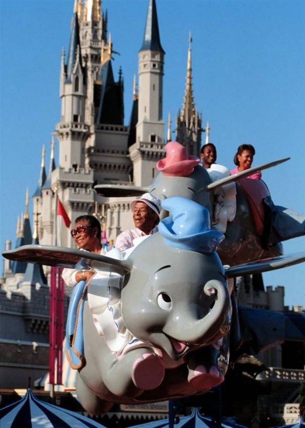 Диснейленд, его вчера и сегодня Счастливые посетители катаются на летающем слоненке Дамбо. Высоту можно регулировать самому с помощью рычага