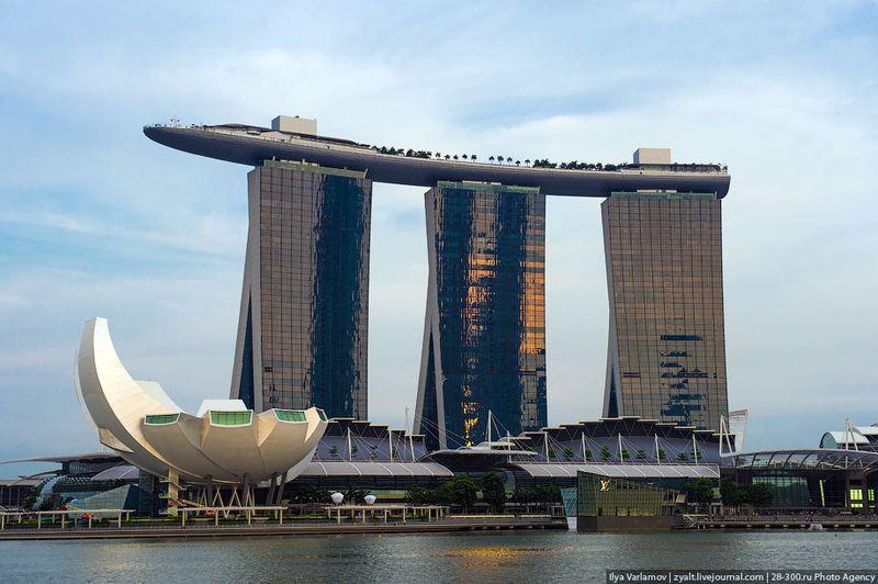 Отель Marina Bay Sands, бассейн под облаками Общий вид. В трех башнях более 2500 номеров. На крыше расположен бассейн. Большая белая лилия - музей современного искусства. У подножия магазины, театр и рестораны.