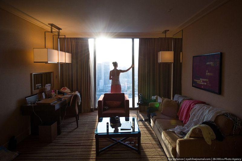 Отель Marina Bay Sands, бассейн под облаками Окно (женщина стоит для масштаба). Диван неудобный.