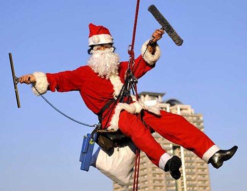 Лучшие Рождественские фотографии Мойщик окон, переодетый в костюм Санта-Клауса на одном из небоскребов в Токио, Япония