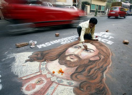 Лучшие Рождественские фотографии Индийский художник заканчивает работу над картиной Иисуса Христа на проезжей части Калькутты