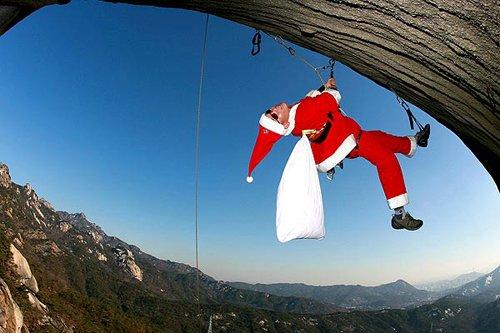 Лучшие Рождественские фотографии Скалолаз, переодетый в костюм Санта-Клауса, неподалеку города Бухан, Южная Корея